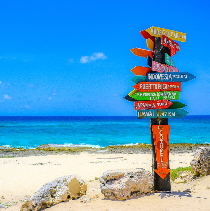 Sign in Cozumel, Mexico by the beach of arrows pointing towards different destinations