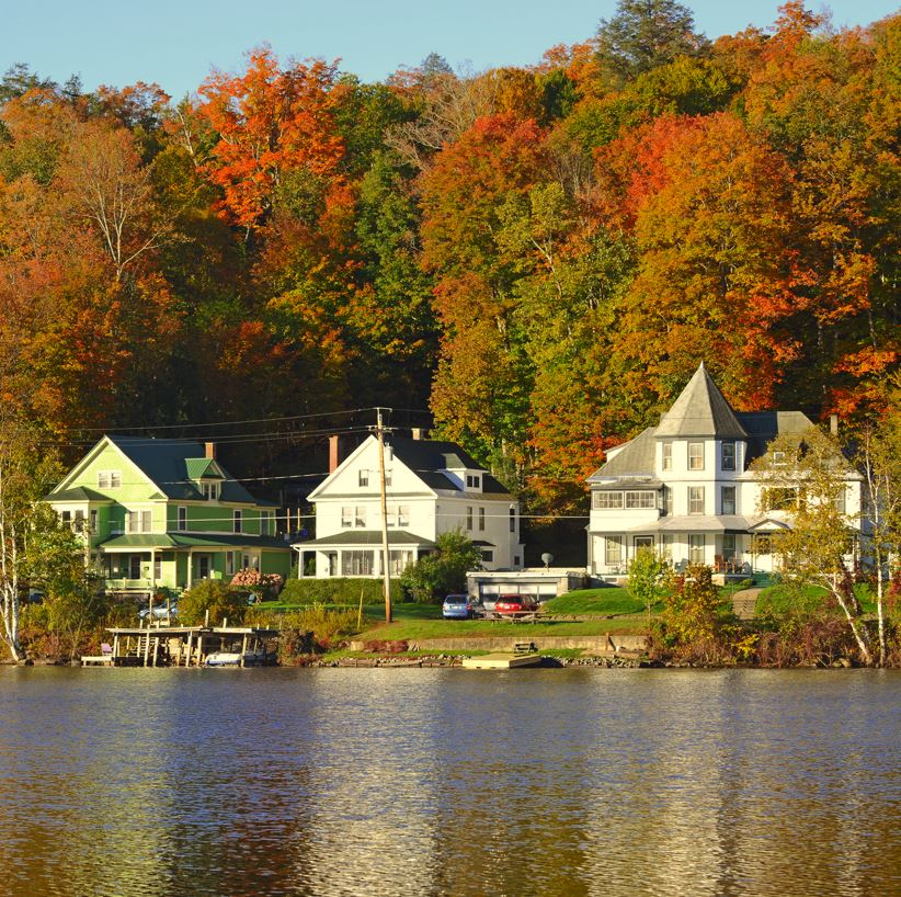 Catskills lakeside houses edged by trees in fall