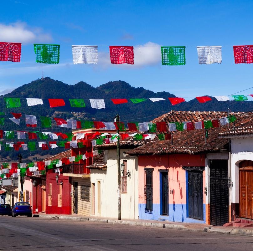 Mexican flag colored papel picado hanging over Guadalupe Street in San Cristobal de las Casas, Mexico