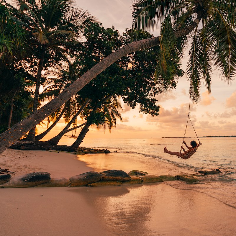 Young adult woman relaxing on a swing in a tropical paradise