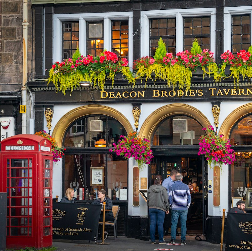 Edinburgh, Scotland, UK - August 24, 2020: View of typical pub or restaurant in the center of Edinburgh. People gathering to eat out in the evening