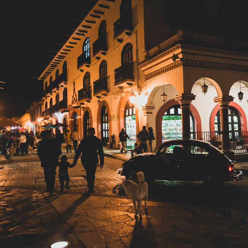 people and dog walking the streets of San Cristobal, Mexico at night