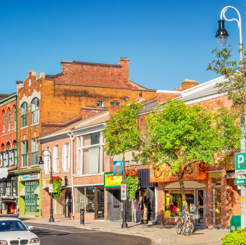 Car drives past stores in downtown St Catharines Ontario Canada on a sunny day