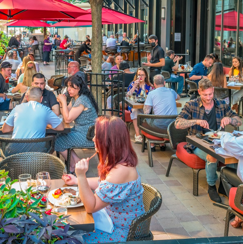 People dine on a restaurant patio in downtown Toronto Ontario Canada on a sunny evening. Proof of vaccination will be required for indoor dining in Ontario starting September 22nd.