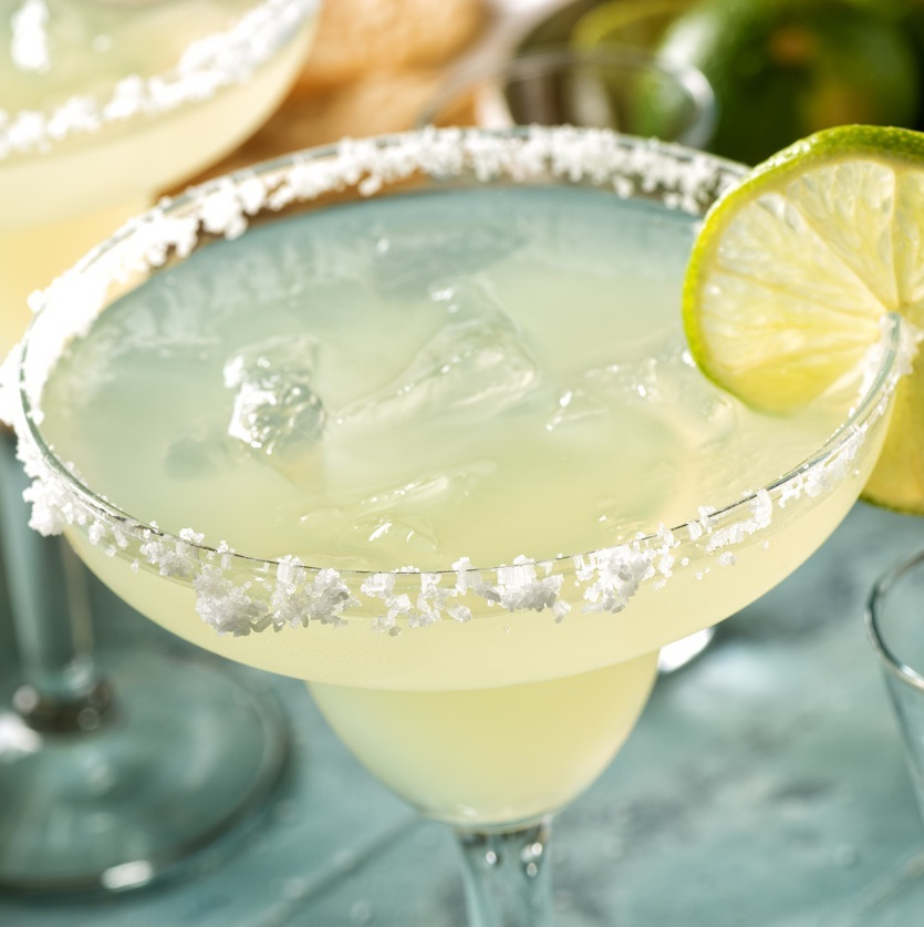 Close up of a tequila and lime margarita with a salted rim on an outdoor table with tortilla chips and pico de gallo.