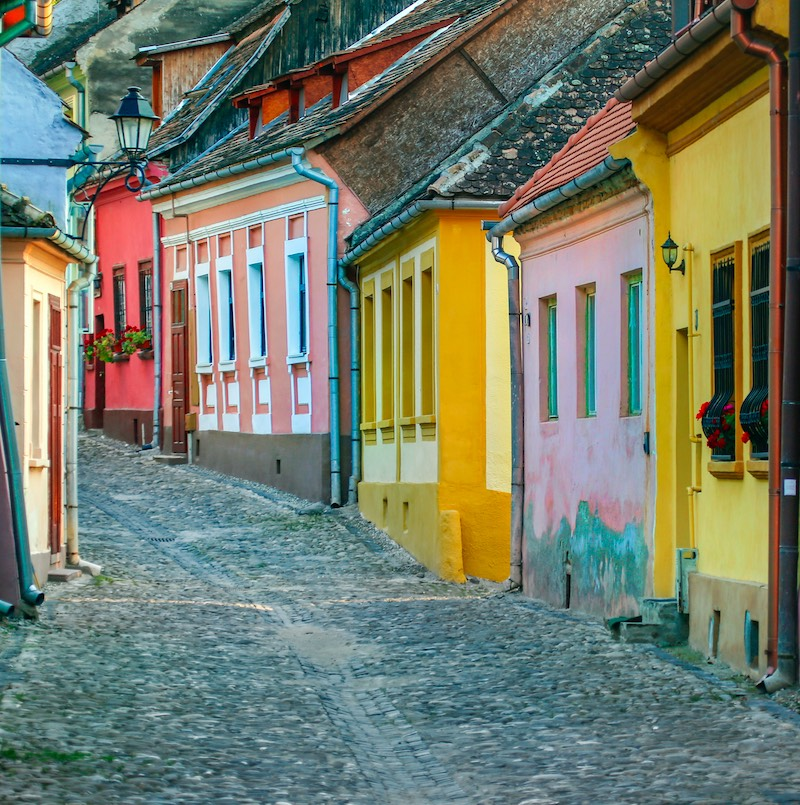 Rustic cobblestone street with colorful houses in old town Sighisoara, Romania