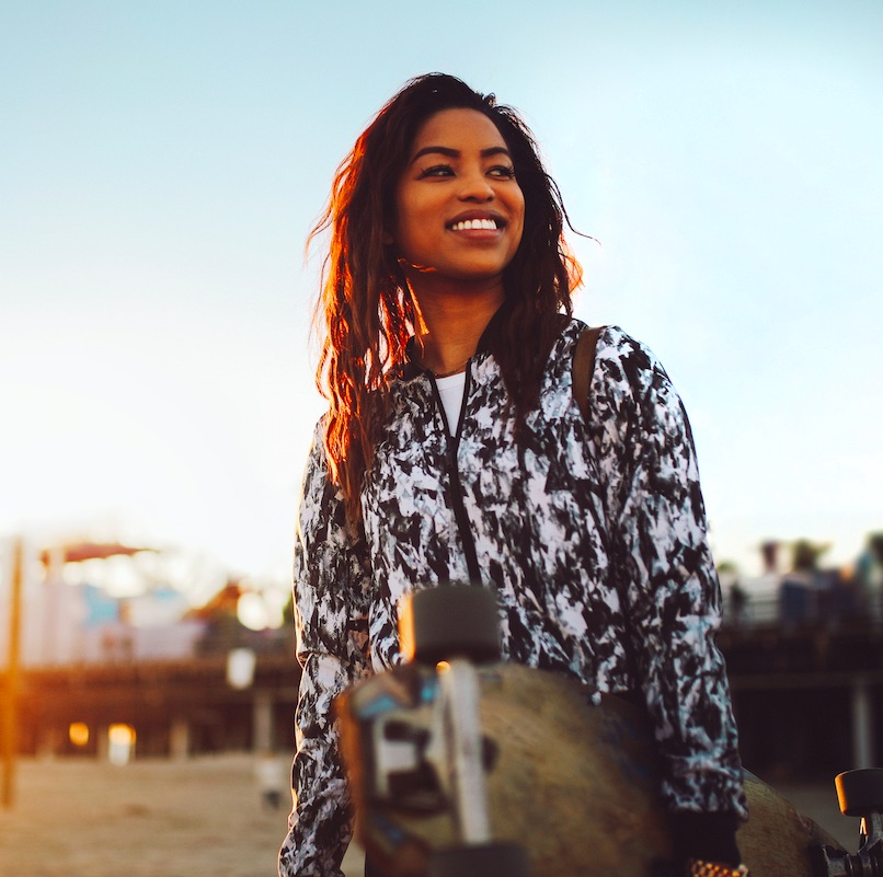 woman smiling and holding a skateboard in Venice Beach