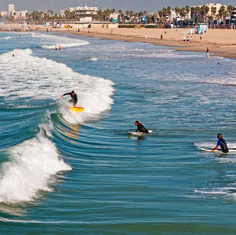 bird's eye view of surfers riding the waves in the Pacific Ocean in Los Angeles, California