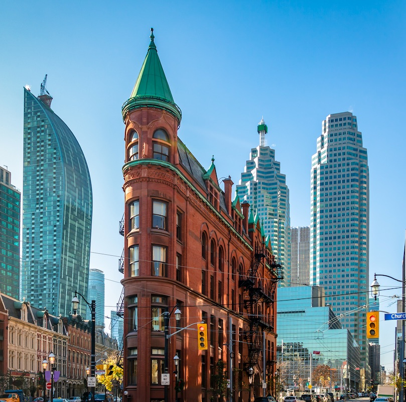 Building in downtown Toronto with CN Tower on background - Toronto, Ontario, Canada. direct flights are available from New Delhi to Toronto