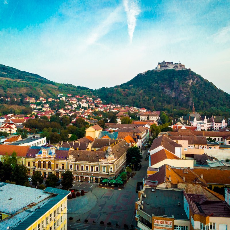 Color image depicting a high angle drone view of the city of Deva, a town in the Transylvania region of Romania. We can see communist-style apartment blocks and Deva's ancient citadel in the distance. The scene is set off by a sunset and cloudscape.