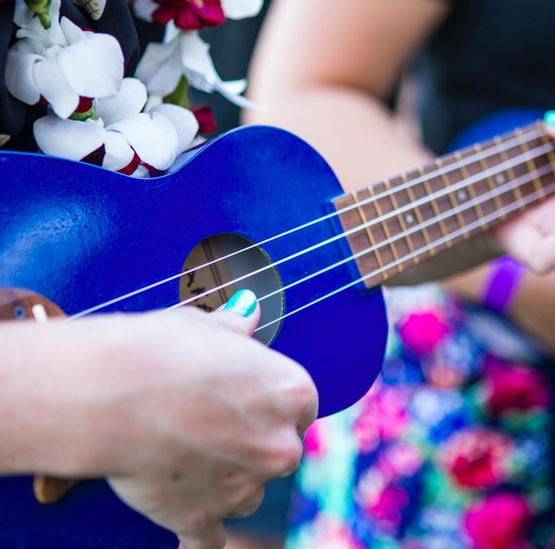 Two women playing music on ukulele in Maui.