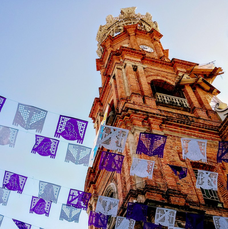 Unusual angle looking up at old brick bell tower and crown of Guadalupe Church in Puerto Vallarta with colorful cut paper flags waving in the breeze.
