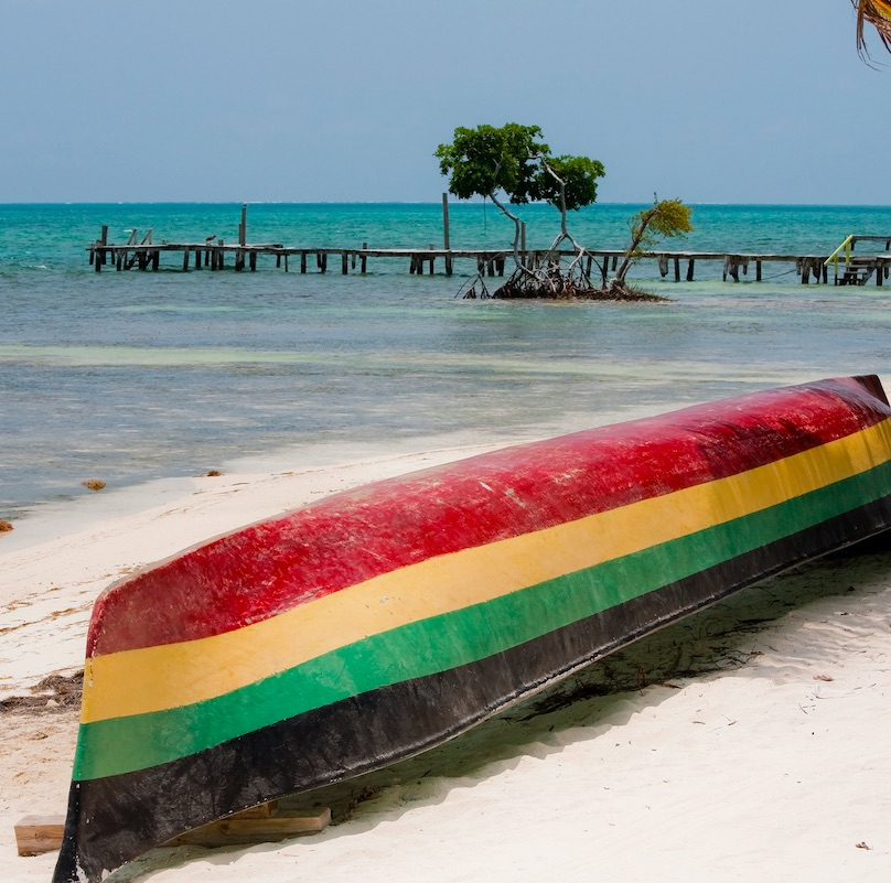 an overturned boat on the beach in the Caribbean. Boat is painted in Rasta colors.