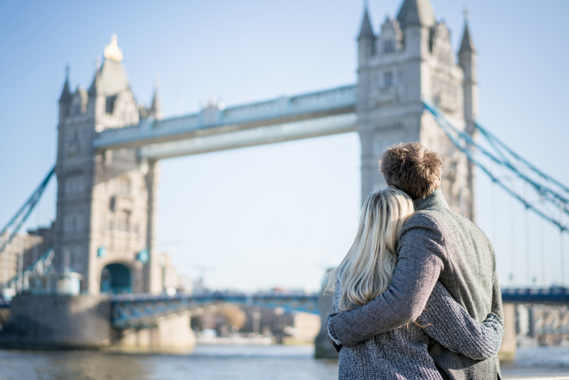 Loving couple sightseeing in London looking at Tower Bridge