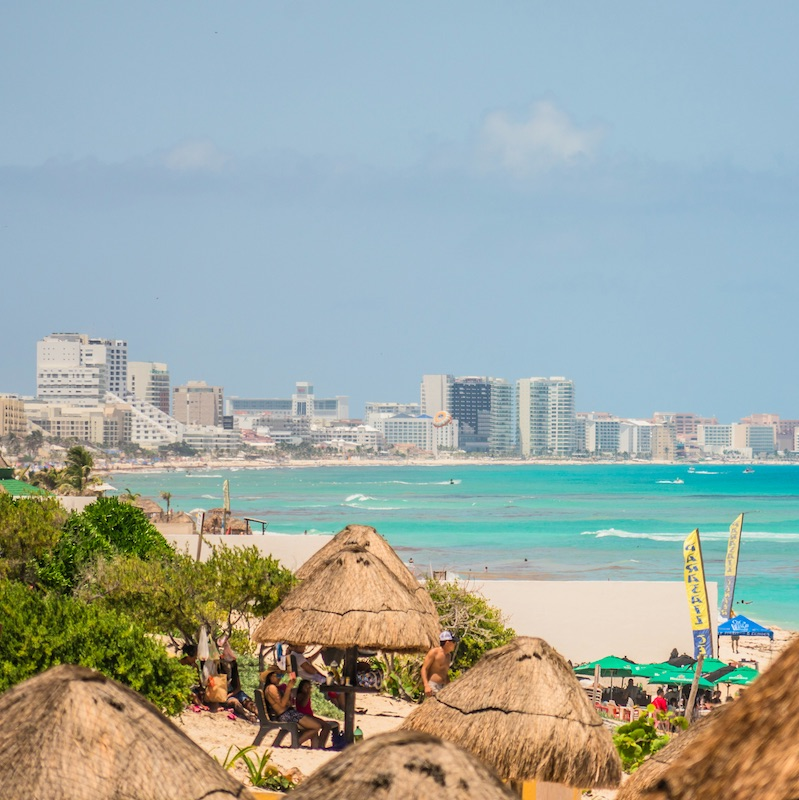 Cancun, Mexico - August 8, 2021: Cancun Hotel Zone - view from Playa Delfines. Hotel Zone in Cancun is the home to all-inclusive resorts, bars, clubs, and white sand beaches. In 2019, Cancun received 6.15 million foreign visitors.