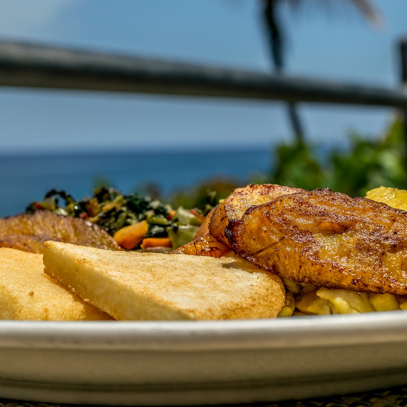 Typical Jamaican breakfast of fried bammy, friend plantain, ackee and sailfish, callaloo. These foods are also eaten for lunch or dinner.