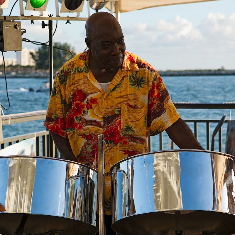 A caribbean musician playing steel drums with the ocean in the background.