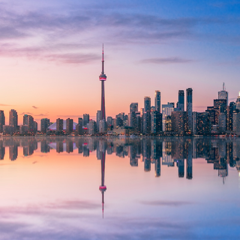 Toronto Skyline at sunset with reflection - Toronto, Ontario, Canada. take a flight from Toronto to Cancun this winter